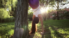 Sporty woman doing yoga exercises with handstand headfirst near the tree. Stock Footage