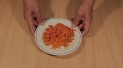 Man puts shredded carrots on the table Stock Footage