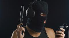 Terrorist in balaclava using smart phone and listening to music Stock Footage