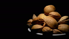 Bowl with almonds nuts in rotation on black background Stock Footage