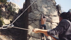 Man climbing the cliff with woman belaying him Stock Footage