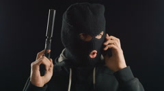 Dangerous terrorist in balaclava talking on the phone. redemption requirement. Stock Footage