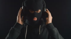 Man in a balaclava listening to music on headphones. He enjoys a music rhythm Stock Footage