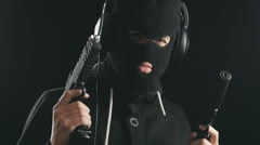 Man in balaclava with gun in hands listening to music on headphones and dancing Stock Footage