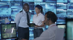 4K Security team watching multiple CCTV video screens in system control room Stock Footage