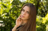 Young woman standing sidwise on the background of trees Stock Photos