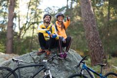Biker couple sitting on rock and pointing in distance Stock Photos