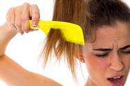 Young woman combing her long ponytail Stock Photos