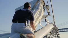 Sailor Releasing Front Sail on the Tagus River Stock Footage
