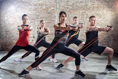 Young people doing workout with elastic band Stock Photos
