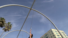 A woman in a black bikini swinging on the traveling rings at Santa Monica beach Stock Footage