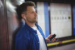 Handsome man listening song on mobile phone Stock Photos