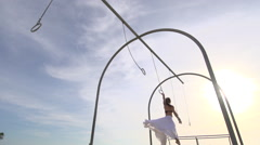 A woman in a white dress swings on traveling rings at Santa Monica beach. Stock Footage