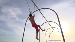 A young man swinging on the traveling rings at Santa Monica beach , slow motion. Stock Footage