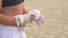 A woman in a white dress preparing to swing on the traveling rings at Santa Moni Stock Footage