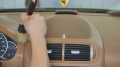 Close up of hand using a brush to clean and remove dust or dirt on the car Stock Footage