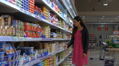 Young woman chooses the cheese in the dairy section at the supermarket Stock Footage