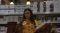Young woman chooses souvenirs in the household section at the supermarket Stock Footage