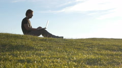 Man using laptop in peaceful countryside Stock Footage