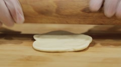 Baker kneading dough with a rolling pin on the table for pies Stock Footage