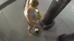 A woman prepares for Muay Thai kickboxing training at the gym. Stock Footage