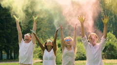 Multicultural group of friends throwing colorful powder over heads at festival Stock Footage