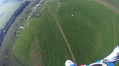 Professional skydiver parachuting above green field. Extreme sport. Landscape Stock Footage