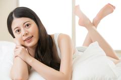 Beautiful Asian young woman lying on bed comfortably and blissfully Stock Photos