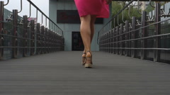 Girl in a pink dress walking through the city Stock Footage
