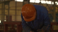 Worker in a Red Helmet at the Factory Saws Grinder Metal. the Face is Not Stock Footage
