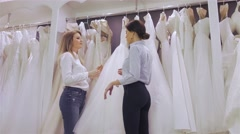 Smiling pretty bride chooses white gown at shop of wedding fashion. Happy Wed Stock Footage