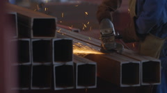 Welder in the Shop on His Haunches Grinder Grinds Steel Product Sparks Fly on Stock Footage