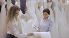 Female shop consultant helps bride chooses dress at shop of wedding fashion Stock Footage