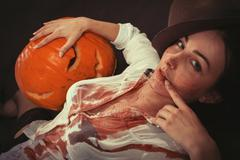 Halloween, woman in blood with pumpkin lying looking at camera, toned image Stock Photos
