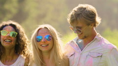 Happy friends dancing at Holi festival, young people covered in powder paint Stock Footage