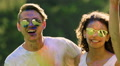Multicultural couples covered in colorful powder enjoying life, smiling, dancing HD Footage