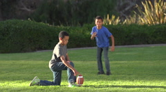 Two brothers kicking a football, super slow motion. Stock Footage