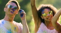Happy guys and girl raising hands, jumping, hanging out at Holi party outdoors HD Footage