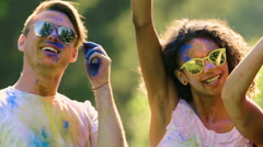 Happy guys and girl raising hands, jumping, hanging out at Holi party outdoors Stock Footage