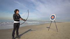 A female archer shooting targets with her bow and arrow , slow motion. Stock Footage