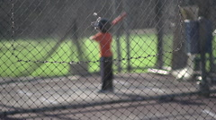 A young boy practicing baseball at the batting cages , slow motion. Stock Footage