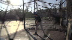 A young man practicing baseball at the batting cages, slow motion. Stock Footage
