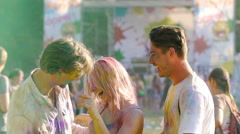 Cheerful young men and woman having fun at concert, friends colored with powder Stock Footage
