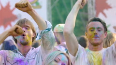 Beautiful woman and two men in powder paint jumping and dancing at Holi party Stock Footage