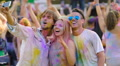 Friends covered in color paint taking photos on smartphone at concert, Holi fest HD Footage