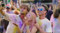 Beautiful girl blowing air kisses for camera, friends filming video at Holi fest HD Footage