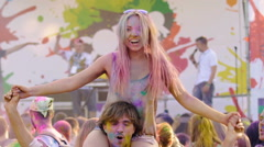 Woman covered in paint sitting on man's shoulders and smiling at Holi festival Stock Footage