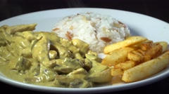Curry sauce chicken with french fries and rice, rotating shot Stock Footage