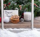 View of a stack of cookies, glass of milk and letter for Santa with evergreen Stock Photos