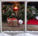 Snowy window view of gift box and Santa cap with burning candle in background Stock Photos